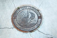 Sanitary sewer cover in downtown Fort Lauderdale. Royalty Free Stock Images