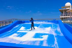 FORT LAUDERDALE, USA - APRIL 30, 2018: Man surfing on the FlowRider aboard the Oasis of the Seas by Royal Caribbean. FORT LAUDERDALE, USA - APRIL 30, 2018: Man Royalty Free Stock Image