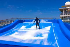 FORT LAUDERDALE, USA - APRIL 29, 2018: Man surfing on the FlowRider aboard the Oasis of the Seas by Royal Caribbean. FORT LAUDERDALE, USA - APRIL 29, 2018: Man Royalty Free Stock Photos