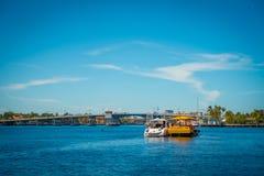 FORT LAUDERDALE USA - JULI 11, 2017: Färgrik gul vattentaxi och vit en yatch som seglar tillsammans, med ett ursnyggt Arkivfoto