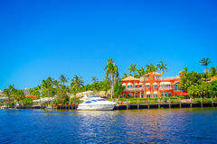 FORT LAUDERDALE, USA - JULY 11, 2017: Beautiful house in the horizont with a riverwalk promenade, highrise condominium Royalty Free Stock Image