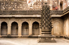 Fort in maheshwar, india with arches and a carved pillar. Interiors of a fort in maheshwar india showing arches in a stone wall and a carved pillar. This is a Royalty Free Stock Image