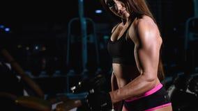 Fort, musculaire, la fille dans des shorts noirs et un dessus, forme un biceps d'une main, soulèvera des haltères de sports L'obs banque de vidéos