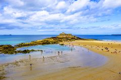 Fort National St Malo Brittany France. Fort National as seen from the walled city of Saint Malo in Brittany France. Holiday makers enjoy the beach sands and rock royalty free stock images
