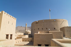 Fort Nizwa, Oman. Fort Nizwa  Oman, with minaret and dom of mosque in background Royalty Free Stock Photo