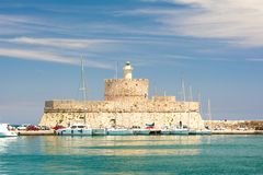 Fort of St. Nicholas with Lighthouse in Mandaki Harbor, Rhodes, Greece. Fort of St. Nicholas with Lighthouse in Mandaki Harbor, Rhodes in Greece stock photo