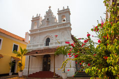 Fort Tiracol. Catholic Cathedral on the background of red flowers. Goa. India. Fort Tiracol. The old fortress by the sea, whose territory is located the Catholic Royalty Free Stock Images