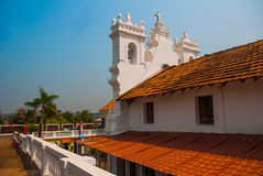 Fort Tiracol. Goa. India. Fort Tiracol. Catholic Church against the blue sky and palm trees. Goa. India Royalty Free Stock Images