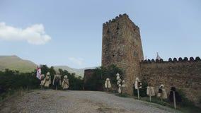 Fortaleza antiga da montanha nas montanhas de Geórgia Torre defensiva da fortaleza e roupa nacional da pele vídeos de arquivo