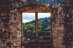 Fortaleza antigua en Alemania Una ventana con un sol de madera ciego del castillo en hermosa vista con las colinas y los bosques  fotos de archivo libres de regalías