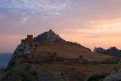 Fortaleza medieval na montanha pelo mar contra o por do sol Fotografia de Stock