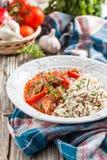 Fortalezca con la pimienta roja, guisada en la salsa de tomate adornada con una mezcla de arroz basmati y salvaje Foto de archivo