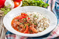 Fortalezca con la pimienta roja, guisada en la salsa de tomate adornada con una mezcla de arroz basmati y salvaje Fotografía de archivo