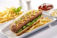 Fortalezca el bocadillo enorme de la salchicha con ensalada de col y salsa de tomate y las fritadas fotos de archivo