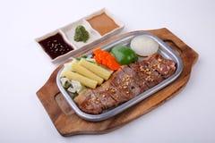 Fortalezca el filete de solomillo en la placa caliente con la salsa triple aislada en wh Imágenes de archivo libres de regalías