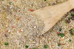 Fortalezca la mezcla condimentada del arroz con una cuchara de madera Foto de archivo