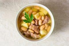 Fortalezca la sopa con las patatas, las habas y los puerros en cuenco de cerámica en el fondo de piedra Foto de archivo libre de regalías
