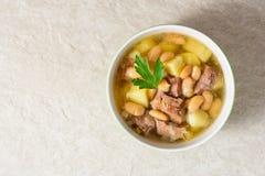 Fortalezca la sopa con las patatas, las habas y los puerros en cuenco de cerámica en el fondo de piedra Imágenes de archivo libres de regalías