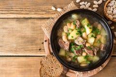 Fortalezca la sopa con las patatas, las habas y los puerros en cuenco de cerámica en el fondo de piedra Fotografía de archivo libre de regalías