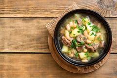 Fortalezca la sopa con las patatas, las habas y los puerros en cuenco de cerámica en el fondo de piedra Fotos de archivo libres de regalías
