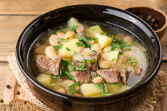 Fortalezca la sopa con las patatas, las habas y los puerros en cuenco de cerámica en el fondo de piedra Foto de archivo