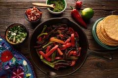 Fortalezca los fajitas en una cacerola con la comida del mexicano de las salsas Fotografía de archivo libre de regalías