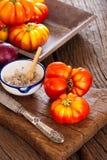 Fortalezca los tomates, el cuenco de la sal con la cuchara y el cuchillo Imagen de archivo