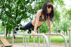 Forte addestramento della donna sulle barre, attività di sport in aria fresca Fotografia Stock