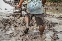 Forte agricoltore asiatico che guida il trattore dell'attrezzo nel campo fangoso, dettaglio dell'agricoltore maschio che cammina  Fotografie Stock Libere da Diritti