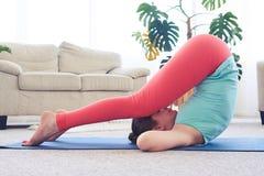 Forte asana di pratica femminile dell'aratro sulla stuoia di yoga Fotografia Stock Libera da Diritti