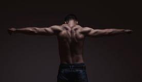 Forte atletico equipaggia indietro su fondo scuro immagine stock