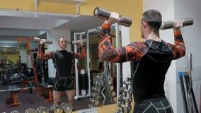 Forte culturista brutale che pompa sui muscoli, facenti gli esercizi in palestra stock footage