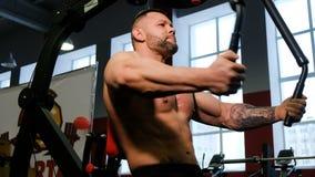 Forte culturista che risolve nella palestra Il sollevatore pesi prepara i muscoli del petto sul simulatore archivi video