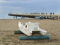 Forte dei Marmi famous pier and patino traditional rowing boat. Forte dei Marmi , Italy _ November 01, 2018: famous pier and traditional rowing boat called royalty free stock photos