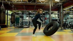 Forte donna atletica che lancia la grande gomma del trattore al rallentatore in palestra video d archivio