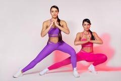 Forte donna atletica, facente esercizio sugli abiti sportivi d'uso del fondo bianco Motivazione di sport e di forma fisica fotografia stock