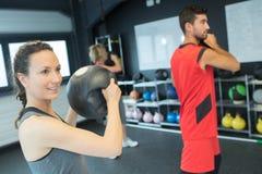 Forte donna in buona salute che tiene palla medica pesante nell'allenamento della palestra Fotografia Stock