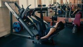 Forte donna castana di forma fisica degli anni medii che fanno gli esercizi sul simulatore 4 K video d archivio