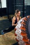 Forte donna che lancia gomma in CrossFit Fotografia Stock