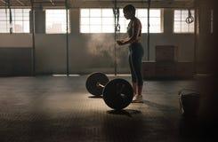 Forte donna che prepara per l'allenamento di sollevamento pesi Immagini Stock