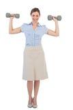 Forte donna di affari che posa con le teste di legno Immagini Stock