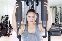 Forte donna di peso eccessivo con la macchina della stampa della spalla Immagini Stock