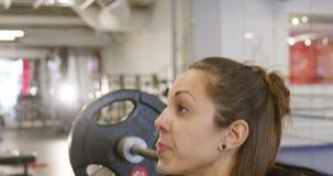 Forte donna motivata che fa allenamento di edifici occupati con i pesi pesanti video d archivio