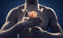 Forte ed uomo adatto che tiene una rosa immagini stock libere da diritti