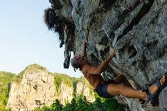Forte ed uomo felice che scala sull'alta roccia sopra il mare con una capanna Fotografie Stock Libere da Diritti