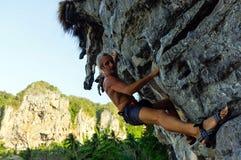Forte ed uomo felice che scala sull'alta roccia sopra il mare con una capanna Spiaggia di Tonsai in Tailandia Immagini Stock Libere da Diritti