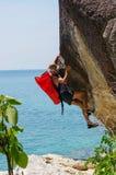 Forte ed uomo felice che scala sull'alta roccia sopra il mare con una h Fotografia Stock