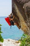 Forte ed uomo felice che scala sull'alta roccia sopra il mare con una h Fotografia Stock Libera da Diritti