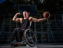 Forte giocatore di pallacanestro nella posa della sedia a rotelle con una palla sulla terra aperta di gioco Immagini Stock Libere da Diritti