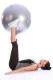 Forte giovane donna che esercita i piedini con la sfera Fotografia Stock Libera da Diritti